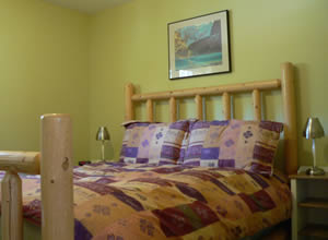 The master bedroom features a queen sized log bed with down duvet
